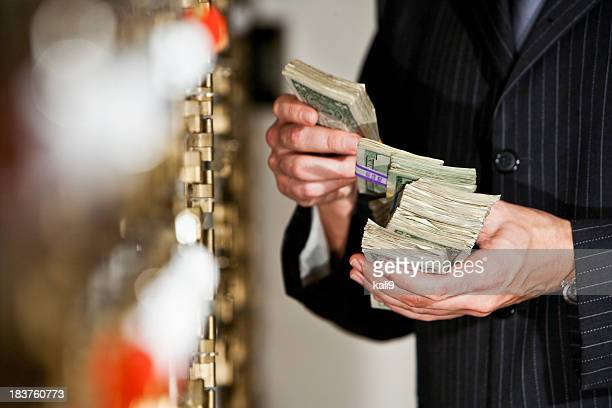 man with cash by safety deposit boxes - money laundering stock photos and pictures