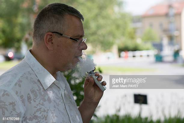 man with casual look smoking e-cigarette - jean marc payet stockfoto's en -beelden