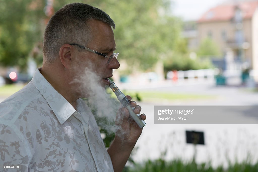 Man with casual look smoking E-Cigarette : Photo