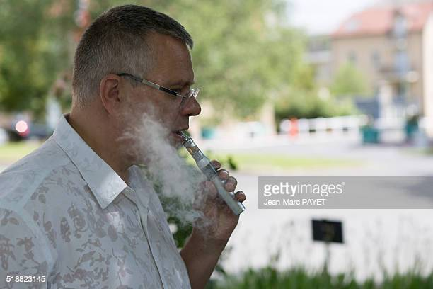 man with casual look smoking e-cigarette - jean marc payet photos et images de collection