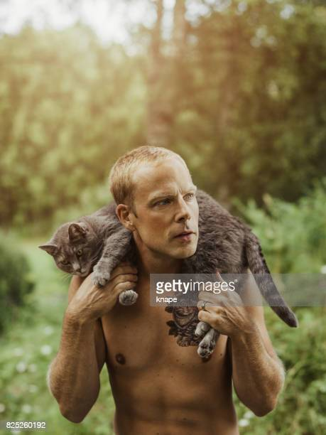 Man with cat tattoo and his pet cat
