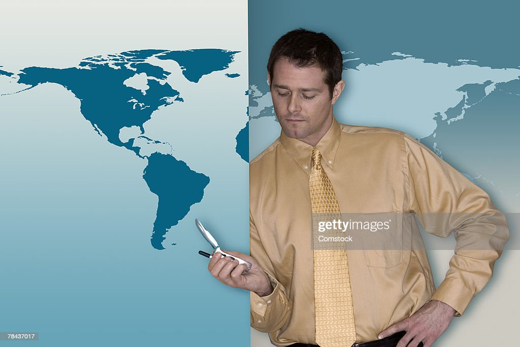 Man with cell phone and world map : Stockfoto