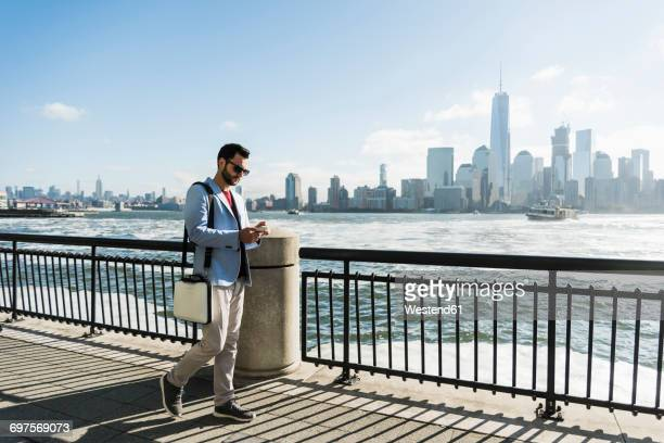 USA, man with cell phone at New Jersey waterfront with view to Manhattan