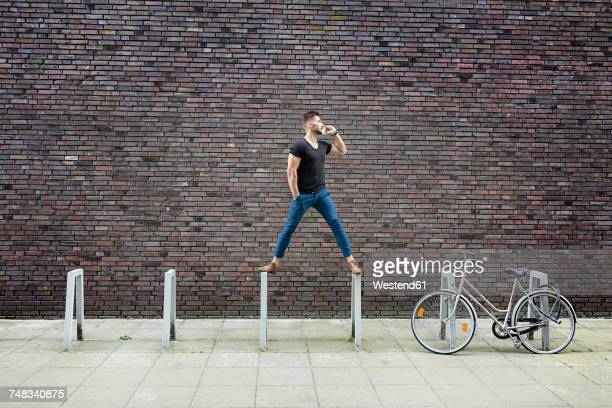 Man with cell phone balancing on bicycle rack in front of brick wall