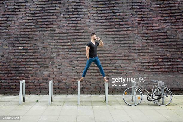 man with cell phone balancing on bicycle rack in front of brick wall - edificios especiales fotografías e imágenes de stock