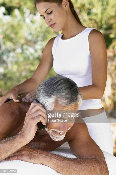 Man with cell phone being massaged