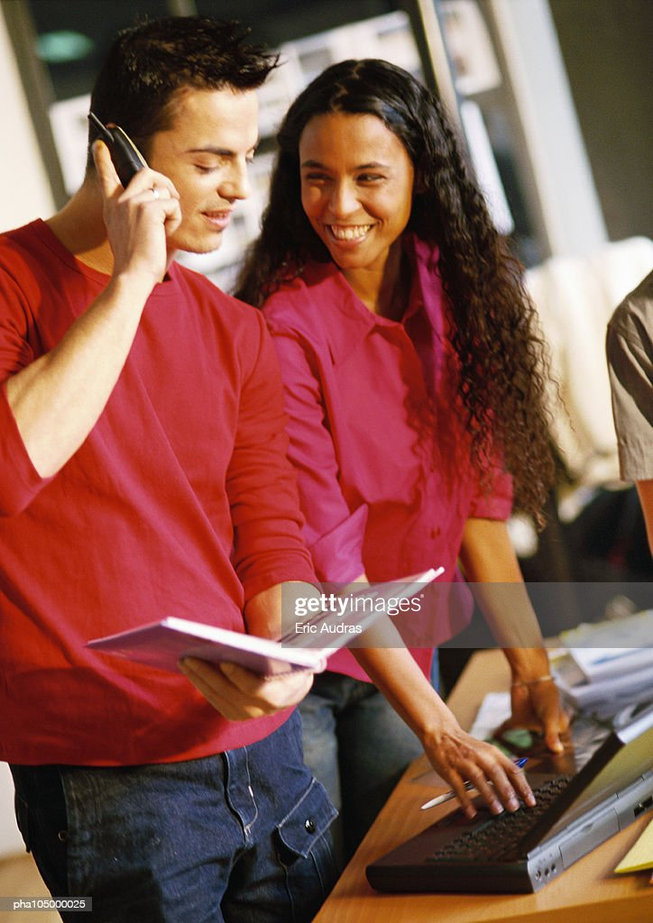 Man with cell phone, woman using laptop computer : Stockfoto