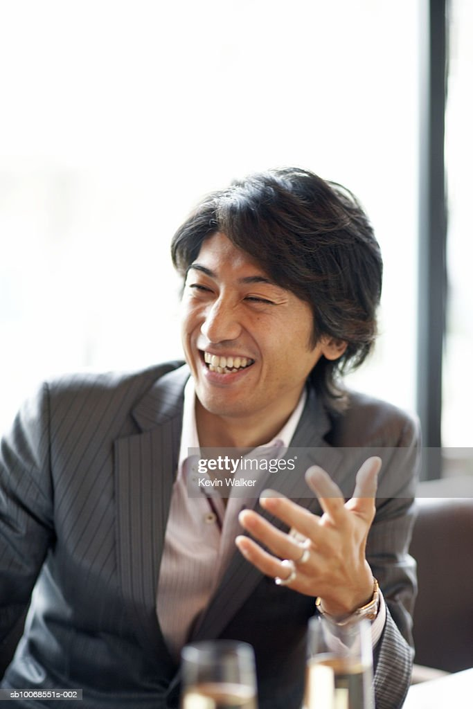 Man with champagne flute at party, smiling : Stock Photo