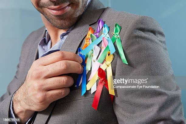 man with charity ribbons on lapel - exceed and excel stock pictures, royalty-free photos & images