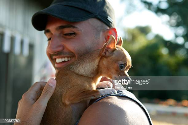 Man with chihuaha on shoulder, smiling