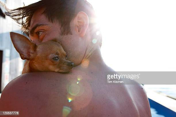 Man with chihuahua on shoulder by pool