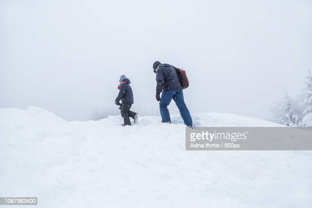 Man with child going through snow