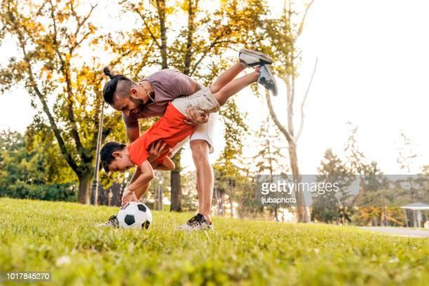mann mit kind fußball spielen auf feld - alleinerzieher stock-fotos und bilder