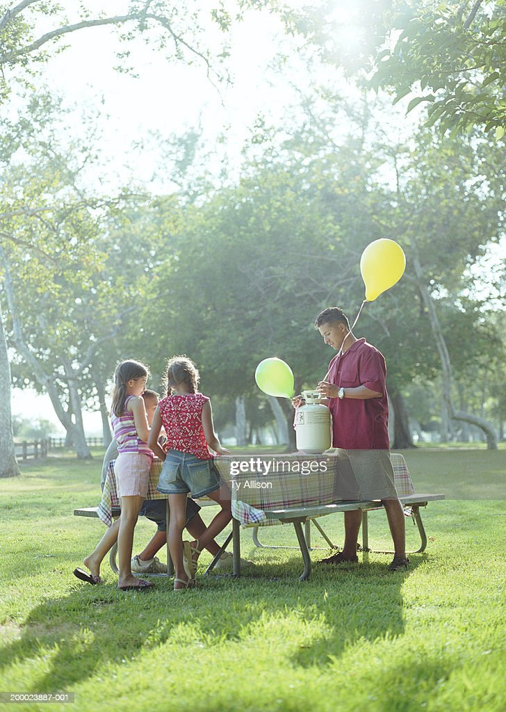 Man With Children Blowing Up Balloons At Picnic Table Stock Photo - 12 person picnic table