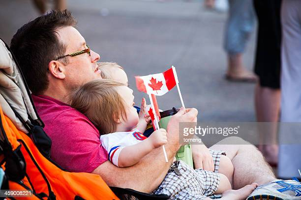 man with children watching parade - flag of nova scotia stock pictures, royalty-free photos & images