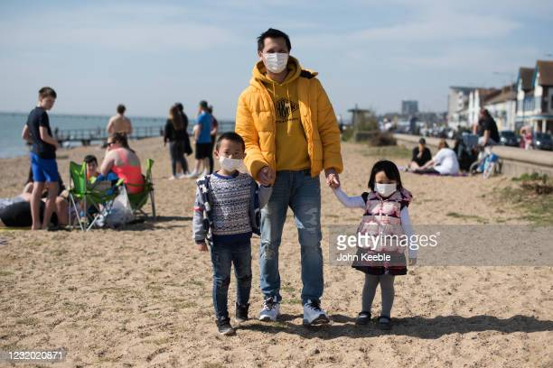Man with children wear face masks as they walk on the beach during the warm weather on March 30, 2021 in Southend, United Kingdom. Despite todays...
