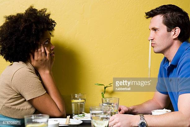 Man with chopsticks in nose at restaurant