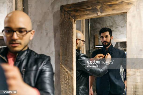 man with client wearing new stylish suit in front of mirror - fashion designer stock pictures, royalty-free photos & images