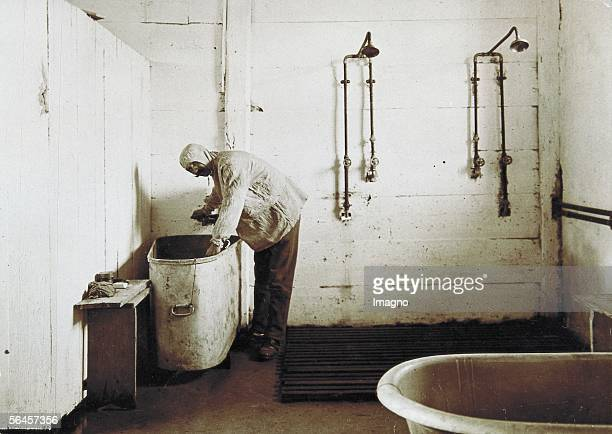 Man with clinging hood standing at a wash tub of a dirty lavatory on the wall two shower heads in the foreground a bath tub Photography around 1910...