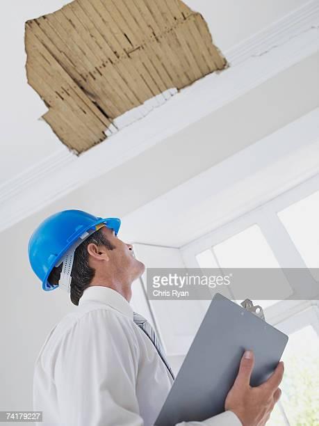 Mann mit Zwischenablage und Helm Suchen Sie in der Decke im Haus