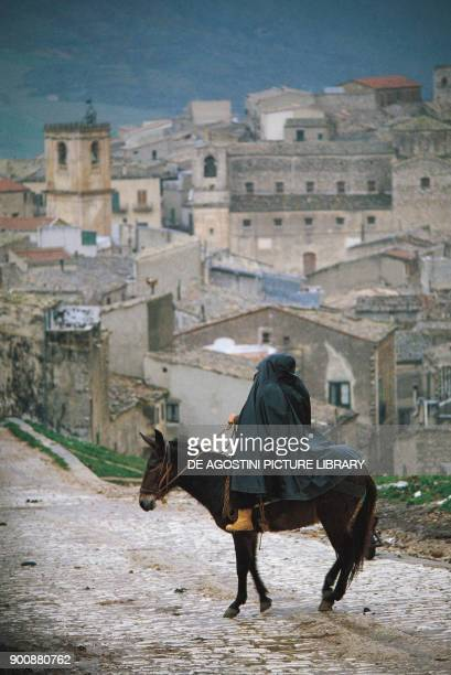 Man with cloak riding a mule Palazzo Adriano Sicily Italy