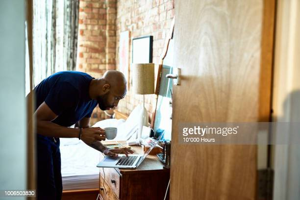 man with coffee checking emails on laptop in bedroom - morgen stock-fotos und bilder
