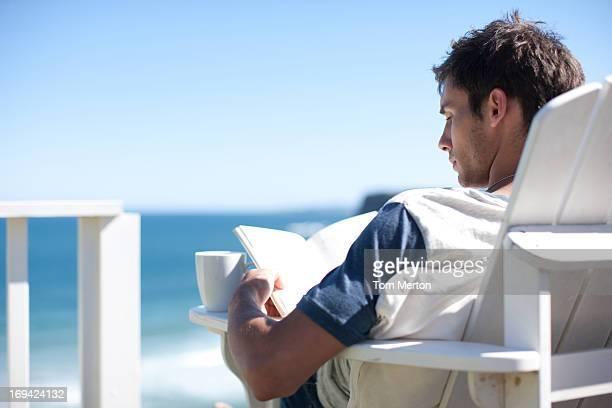 男性、コーヒーカップのデッキチェアで読書を一望 - アウトドアチェア ストックフォトと画像