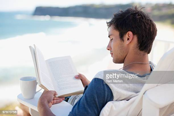 Man with coffee cup reading book in deck chair overlooking ocean