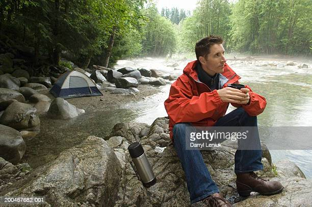 Man with coffee cup sitting atop rock beside river, looking away