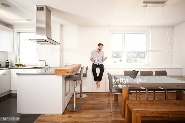 Man with coffee cup sitting on sideboard in his open plan kitchen looking at smartphone