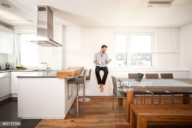 man with coffee cup sitting on sideboard in his open plan kitchen looking at smartphone - ein mann allein stock-fotos und bilder