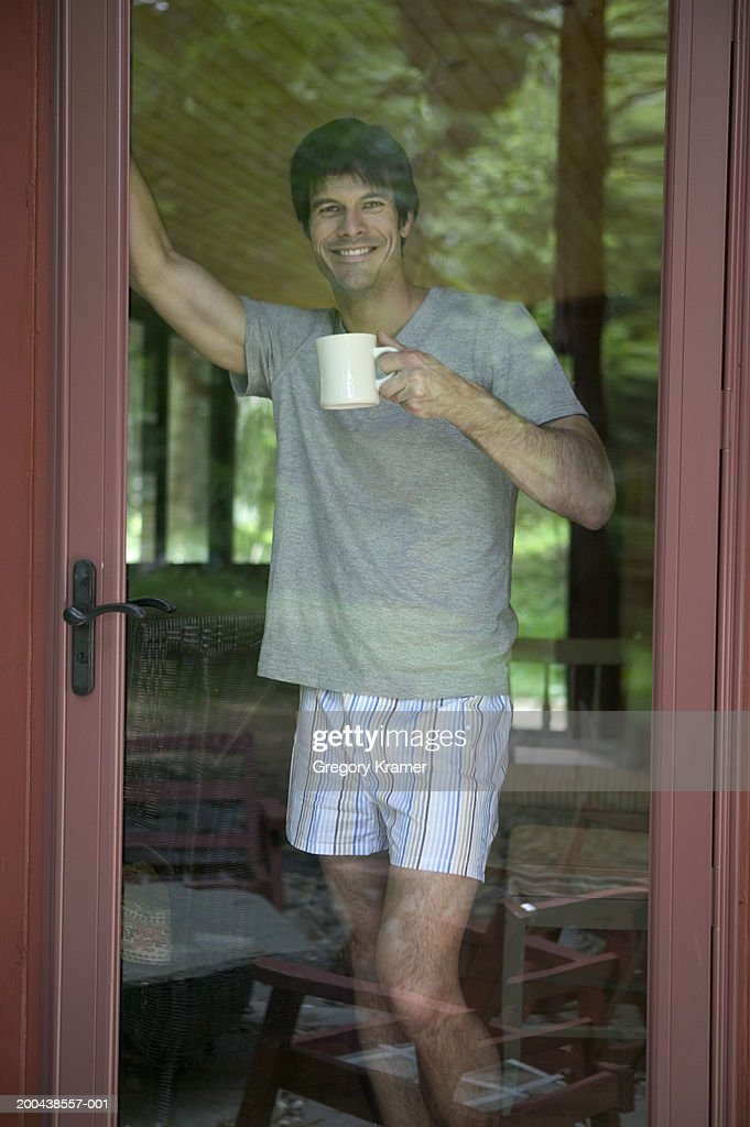 Man With Coffee Mug Looking Out Glass Door Smiling Stock Photo