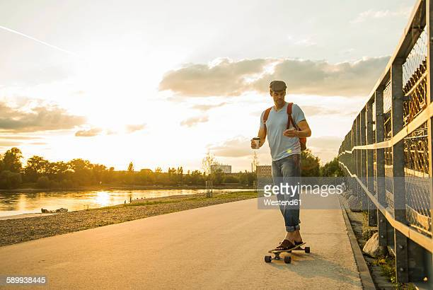 Man with coffee to go and smartphone standing on skateboard in the evening twilight