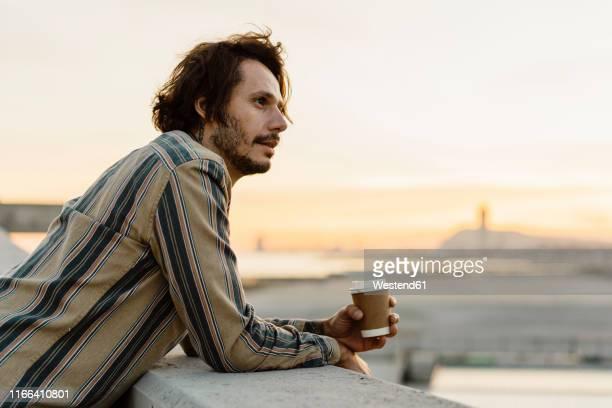 man with coffee to go relaxing at sunset, barcelona, spain - un solo hombre fotografías e imágenes de stock