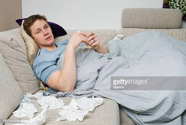Man with cold lying on sofa