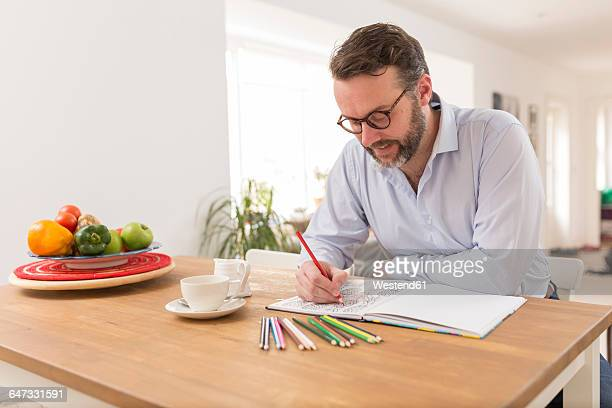 man with colouring book and coloured pencils sitting at wooden table - colouring book stock pictures, royalty-free photos & images