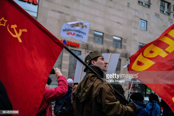 Man with communist flag at the Annual LiebknechtLuxemburg leftwing demonstration in Berlin Several thousand people recalled Rosa Luxemburg and Karl...