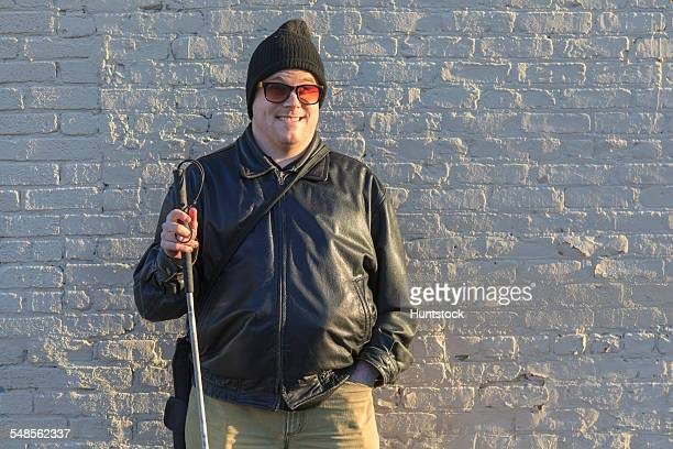 Man with congenital blindness standing in front of a wall with his cane