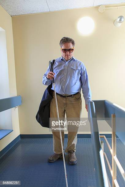 man with congenital blindness using his cane in an apartment hallway - 視覚障害 ストックフォトと画像