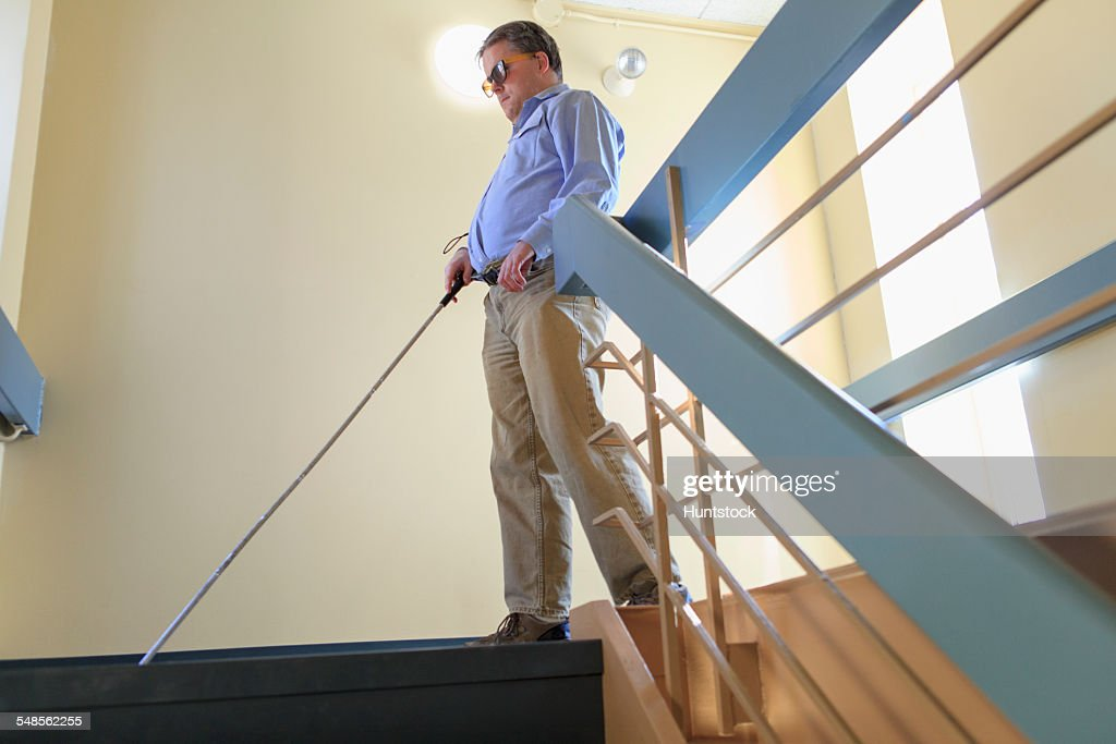 Man with congenital blindness using his cane to go down a stairwell : Stock Photo