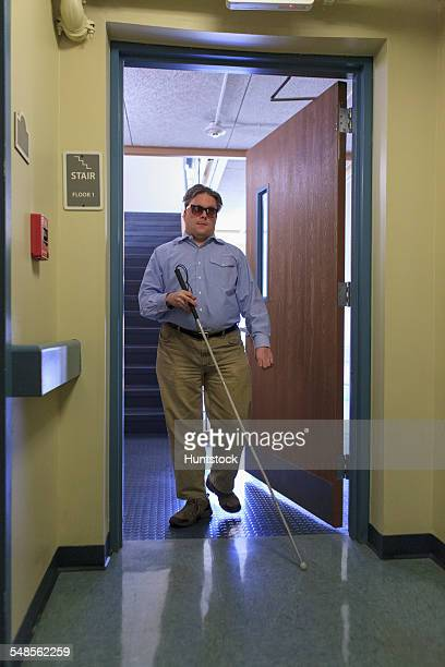 Man with congenital blindness using his cane to go through a doorway