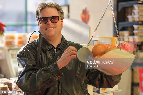 man with congenital blindness weighing fruit at the grocery store - 視覚障害 ストックフォトと画像