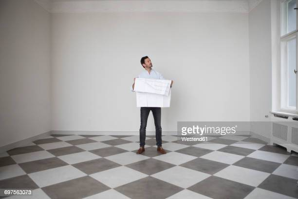 Man with construction plan in an empty room looking up