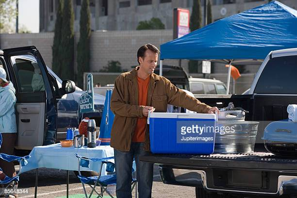 Man with cooler at tailgate party