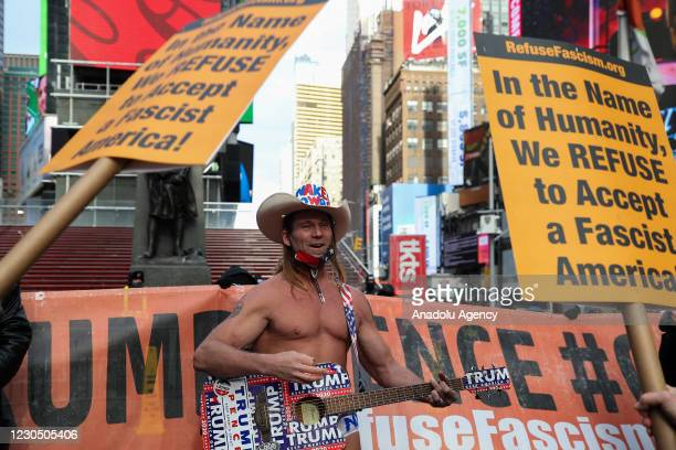 """Man with cowboy hat known as """"Naked Boy"""" stands as protesters are gathered at the Times Square to protest President Trump in New York City, United..."""