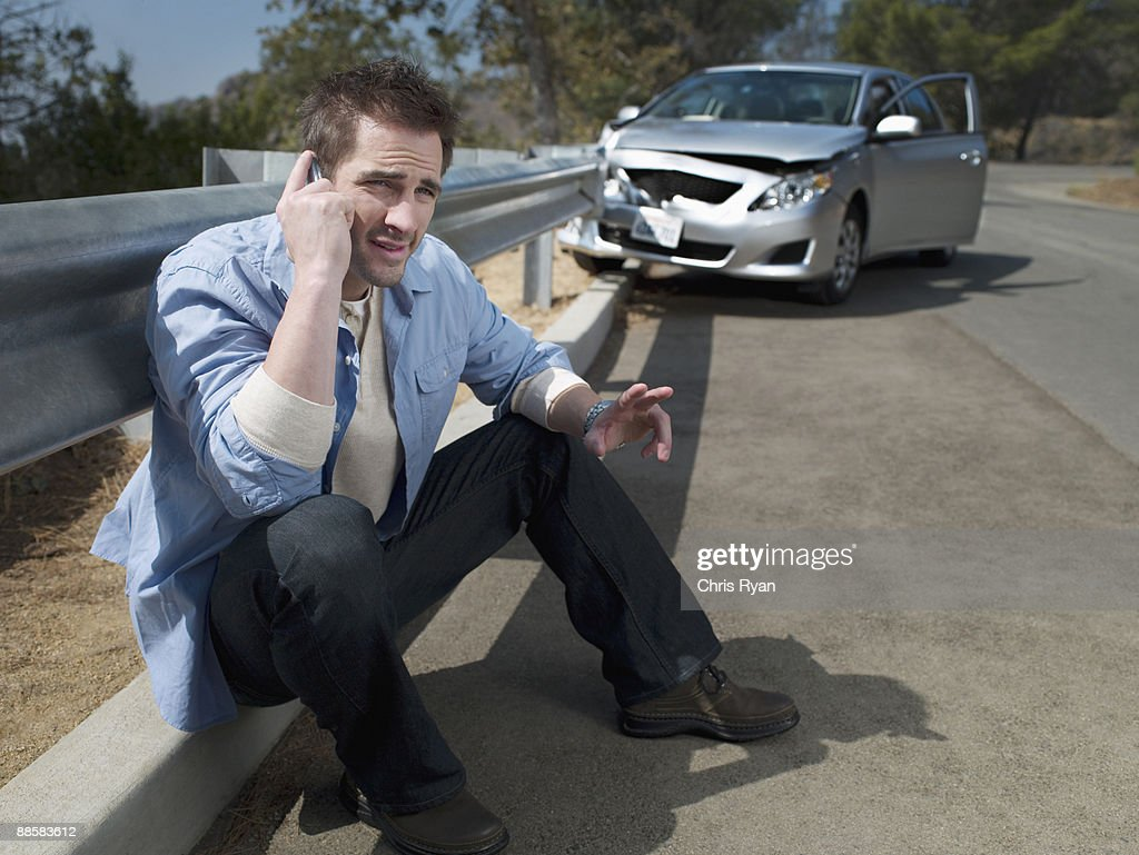 Man with crashed car calling for roadside assistance, : Stock Photo