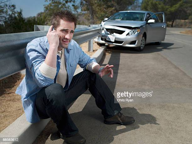 man with crashed car calling for roadside assistance, - curb stock pictures, royalty-free photos & images