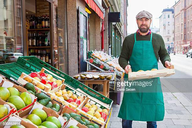 Man with crate in front of greengrocer's shop