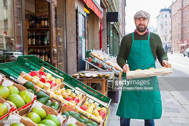 Man with crate in front of greengrocers shop