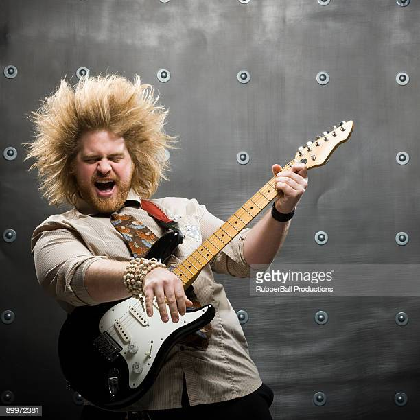 man with crazy hair playing electric guitar